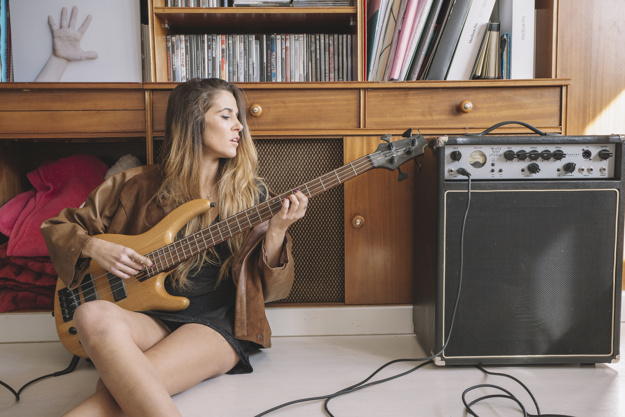 young-woman-playing-guitar-floor_23-2147769065
